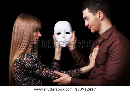 Fashion Happy Couple in Love holding a white mask face. Psychological concept. Duality look at relationships. - stock photo