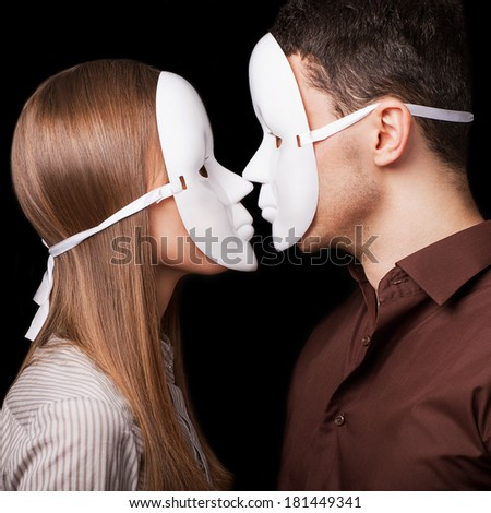 Fashion Happy Couple in Love holding with mask face. Psychological concept. Duality look at relationships. - stock photo