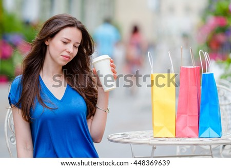 Fashion happy girl with bags after shopping drinking coffee in open air cafe. Sale, consumerism and people concept. Caucasian girl enjoy warm day in outdoor cafe. - stock photo