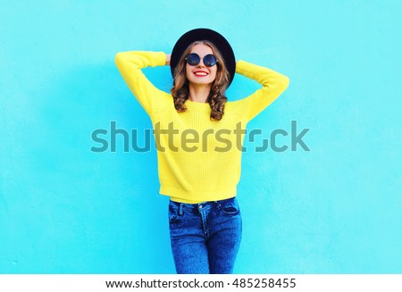 Fashion happy pretty smiling woman wearing a black hat and yellow knitted sweater over colorful blue background