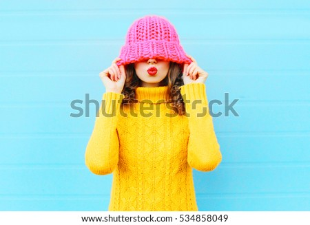 Fashion happy woman blowing red lips makes air kiss wearing a knitted hat, yellow sweater over blue background