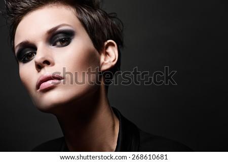 Fashion head shot of brunette woman with short hair cut on black background. Smokey eyes make up - stock photo