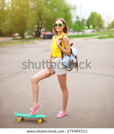Fashion hipster cool girl in sunglasses with skateboard having fun outdoors  - stock photo