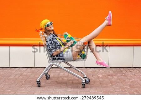Fashion hipster cool girl with skateboard in shopping cart having fun against the colorful orange wall - stock photo