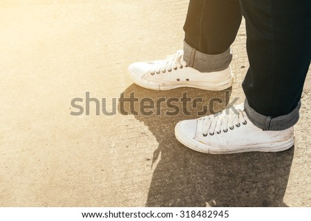 Fashion hipster cool man with white sneakers on the ground concrete - stock photo