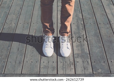 Fashion hipster cool man with white sneakers, soft vintage toned colors - stock photo