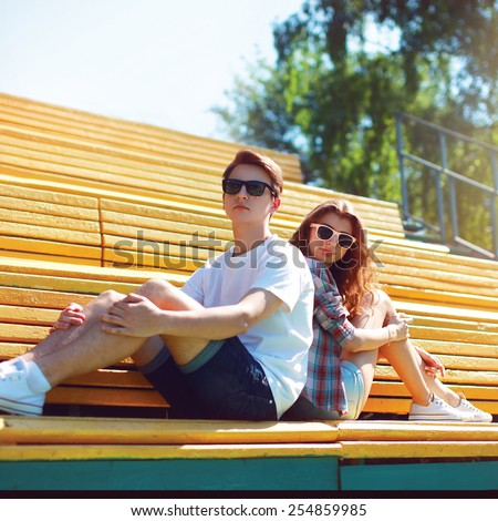 Fashion hipster couple in sunglasses sitting on the bench city park in sunny summer day - stock photo