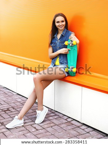 Fashion hipster pretty cool girl with skateboard having fun against the orange wall - stock photo