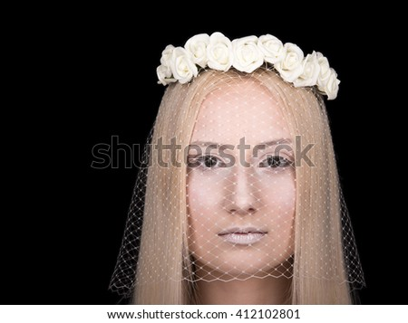 Fashion image closeup. The face of a young lady with a veil and a wreath of roses on his head. A stern glance. Black background - stock photo
