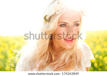 Fashion image of beautiful woman in rapeseed field, wearing flowers in hair - stock photo