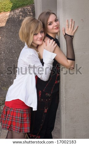 Fashion image of two teen models posed against a concrete wall.