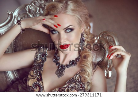 Fashion indoor portrait of beautiful sensual blond woman with makeup in luxurious dress with bijou, posing on modern armchair with sliver frames. - stock photo