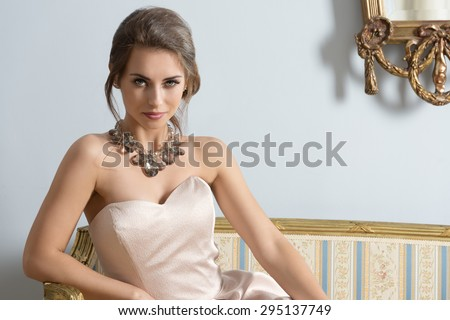 fashion indoor portrait of pretty brunette girl with aristocratic style sitting on ancient sofa with classic hair-style, wearing pink elegant dress and shiny necklace. Smiling and looking in camera  - stock photo