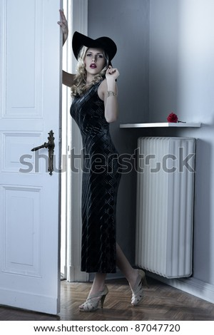 fashion indoor shot of a beautiful blond curly haired girl with long elegant black dress and a black hat near old fashioned door - stock photo
