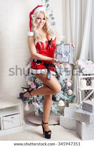 fashion interior photo of beautiful sexy girl with blond hair wears luxurious dress,holding gift in hand,posing near Christmas tree - stock photo