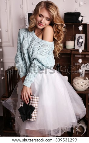 fashion interior photo of beautiful young woman with blond hair and charming smile, wears cozy knitted cardigan and skirt,posing beside Christmas tree and presents  - stock photo