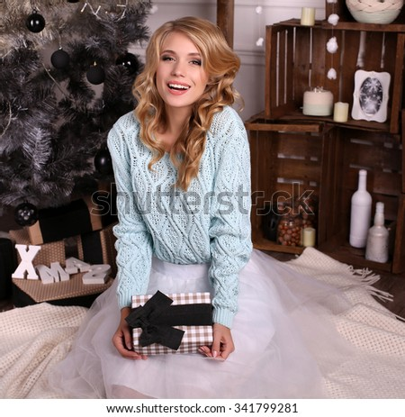 fashion interior photo of beautiful young woman with blond hair and charming smile, wears cozy knitted cardigan and skirt,posing beside Christmas tree and presents