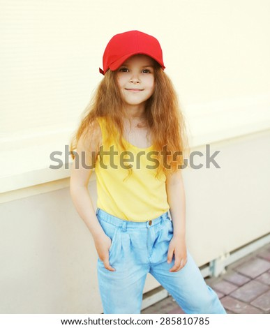 Fashion kid concept - portrait of stylish little cute girl child wearing a cap outdoors in the city - stock photo