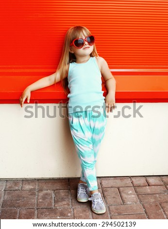 Fashion kid concept - stylish little girl child wearing a t-shirt and sunglasses posing against the colorful red wall - stock photo