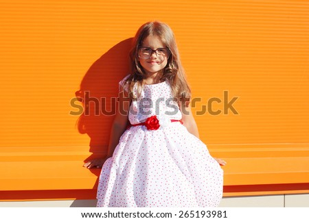 Fashion kid, portrait of beautiful little girl in white dress against the bright wall - stock photo