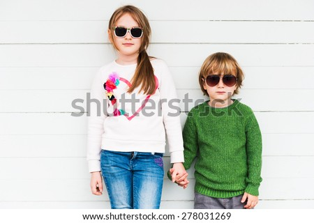 Fashion kids outdoors, wearing pullovers and sunglasses