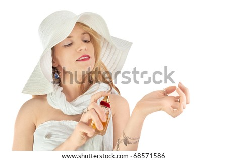 Fashion lady applying perfume in white dress with white hat - stock photo