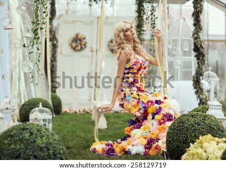 Fashion lady in spring scenery wearing flower dress - stock photo