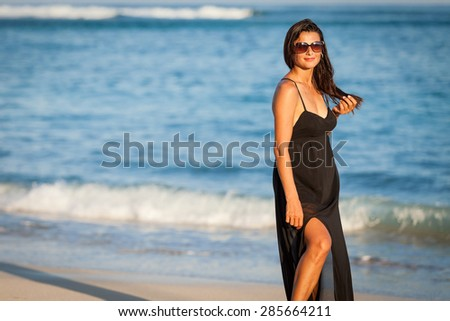 Fashion Lifestyle, Beautiful brunette girl in the sunglasses and black dress on the beach at the day time. Travel and Vacation.