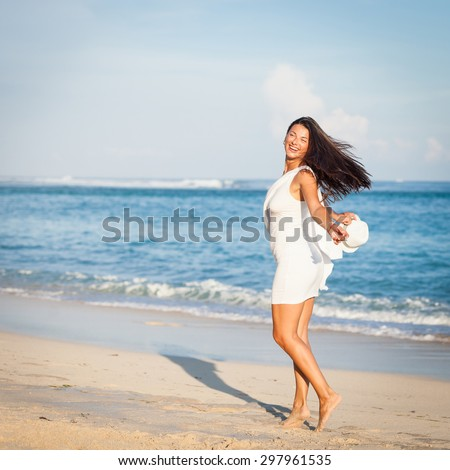 Fashion Lifestyle, Beautiful brunette girl in the sunglasses and white hat walking on the beach at the day time. Travel and Vacation. - stock photo