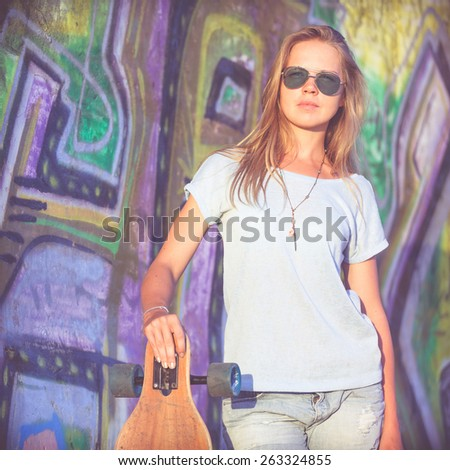 Fashion lifestyle, Beautiful young blonde woman with skateboard standing near the wall with graffiti at the day time.