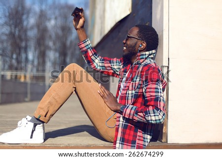 Fashion lifestyle photo happy young african man makes self-portrait on the smartphone outdoors, hipster wearing a red plaid shirt and sunglasses having fun in the city - stock photo