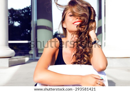 Fashion lifestyle portrait of young happy pretty woman laughing and having fun on the street at nice sunny summer day, listening favorite music at earphones,stylish vintage outfit,bright fresh colors. - stock photo