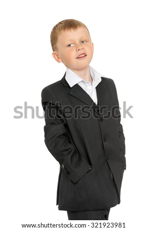 Fashion little blonde boy in a grey suit standing broadside to the camera . The boy stuck his hands in his pockets . Closeup-Isolated on white background
