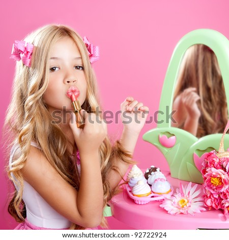 fashion little doll girl in pink vanity mirror with lipstick - stock photo