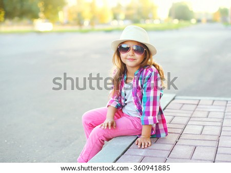 Fashion little girl child wearing a checkered pink shirt, hat and sunglasses in city