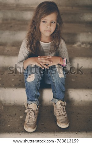 fashion little girl sitting on the stairs