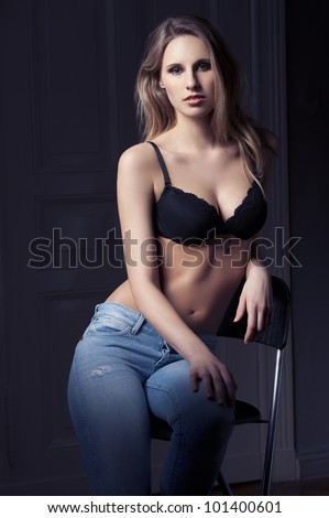 fashion low key shot of beautiful hot blond lady in black bra lingerie and jeans on dark indoor backgound - stock photo