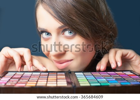 Fashion makeup. Closeup glamor woman with professional cosmetic set with every color imaginable! Colorful palette