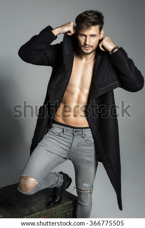 Fashion male model in black coat - stock photo