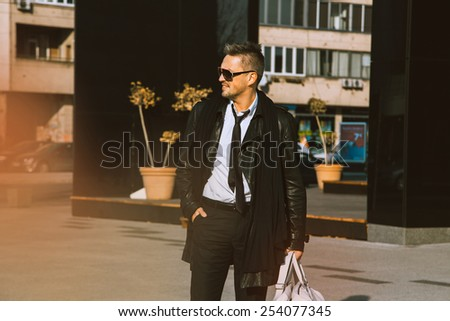 Fashion male model looking away and smiling in leather jacket outdoors at daytime - stock photo