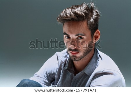 fashion male model looking serious while sitting on a gray background - stock photo