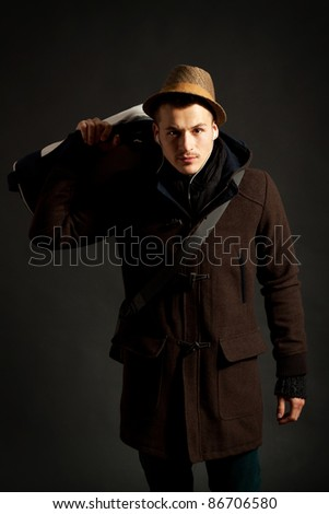 fashion male portrait with a hodded coat and a hand bag on his shoulder - stock photo