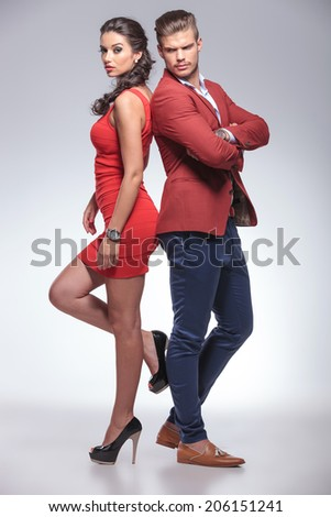 fashion man and woman standing back to back in studio - stock photo