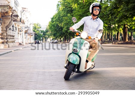 Fashion man driving a scooter in helmet in old town - stock photo