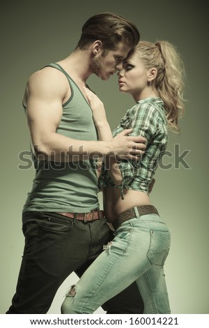 fashion man embracing his girlfriend in a passionate pose, vintage look - stock photo