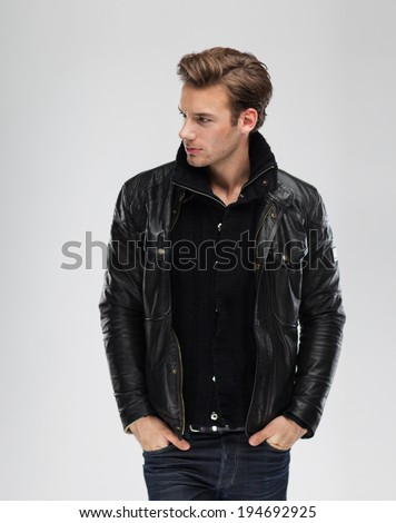 Fashion man, Handsome serious beauty male model portrait wear leather jacket, young guy over gray background - stock photo