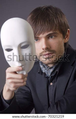 fashion man hiding his face under white mask - stock photo