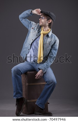 fashion man in denim clothes sitting on old suitcase - stock photo