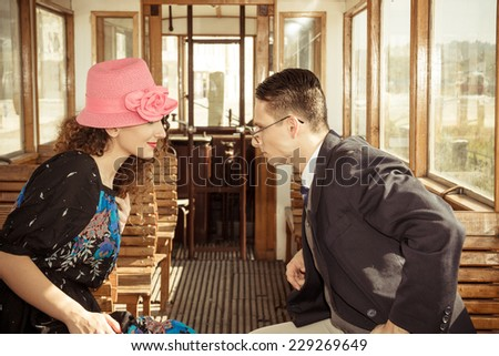 fashion man in suit in the wagon train  with smiling woman look at each other face to face , love talk of couple on train , vintage retro fashion photo - stock photo