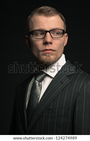Fashion man in suit wearing glasses. Studio shot.